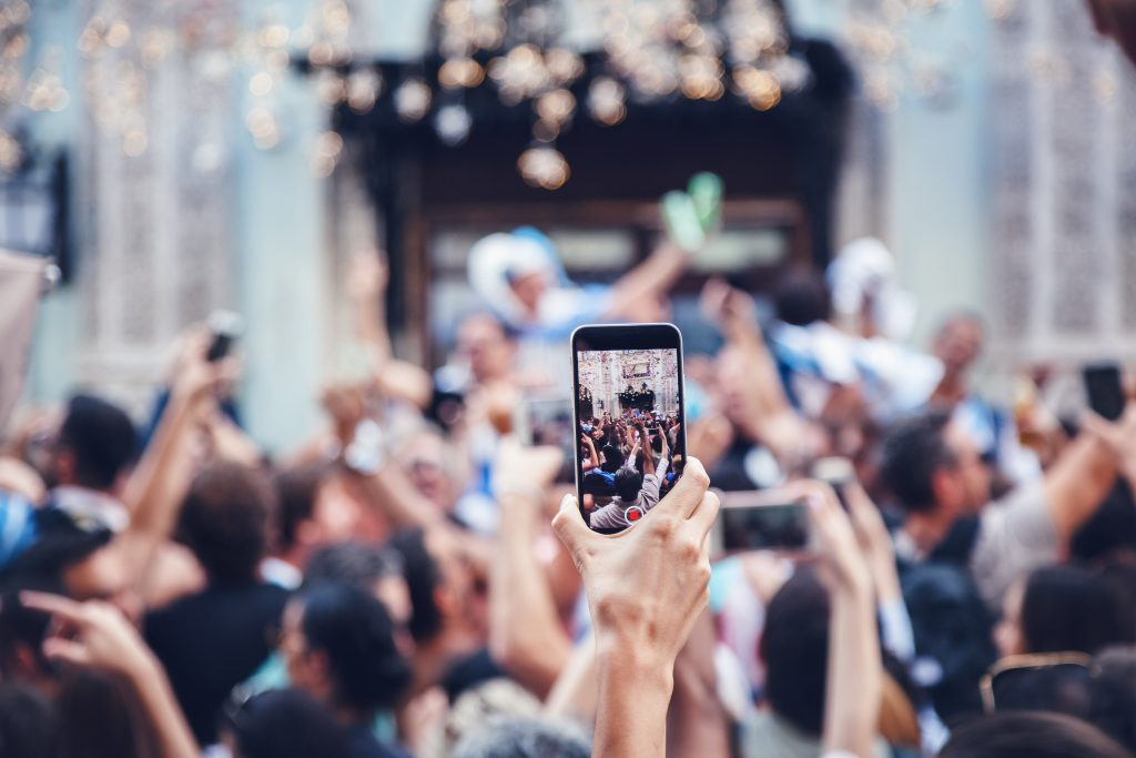 What is the purpose of photography? Hand holding camera phone above crowd to photograph proceedings.